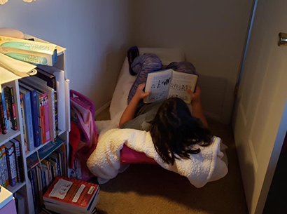 Student reading a book at home.