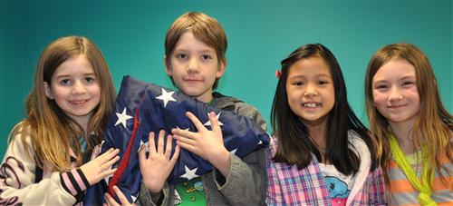 Four students holding a folded American flag
