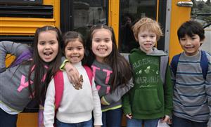 Five elementary students in front of a bus
