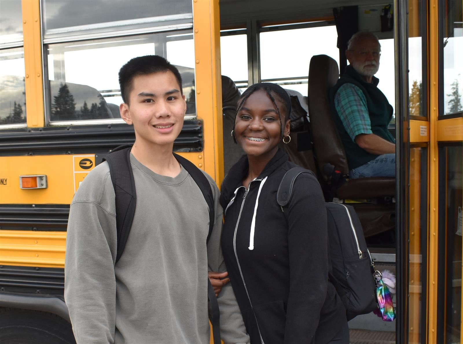 Two students posing in front of a bus.