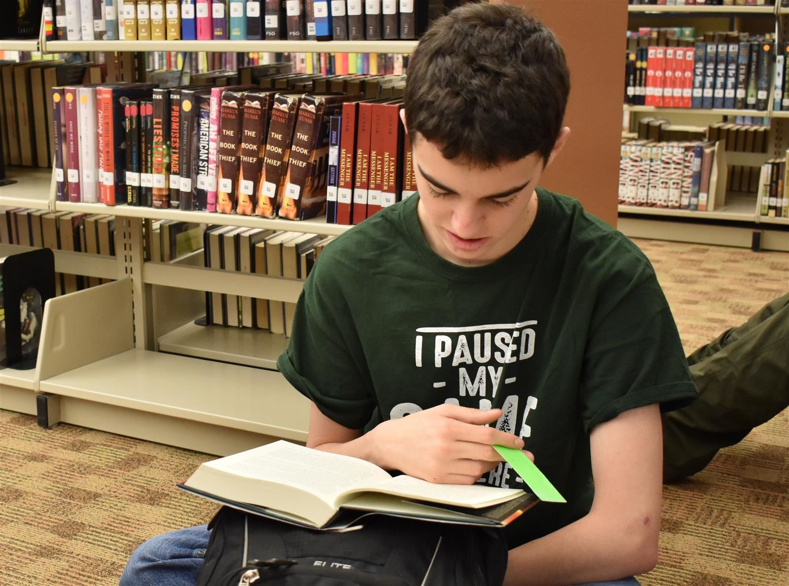 high school student reading a book in the school library