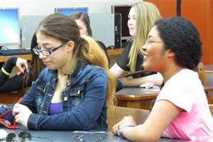 Two centered female students listing to a presentation. One is wearing a jean jacket the other a pink shirt.