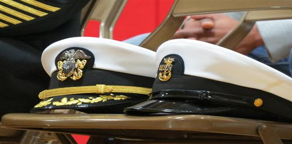 two naval officers hats on a chair